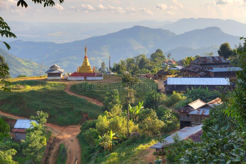 有金黄的stupa的村庄青山 库存照片