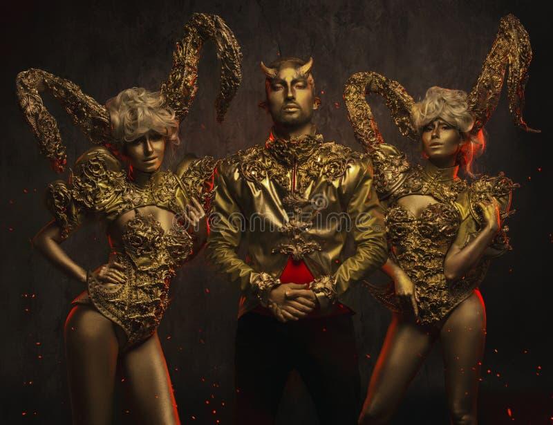 有金黄装饰垫铁和英俊的恶魔人的美丽的恶魔妇女装饰夹克的 免版税库存图片