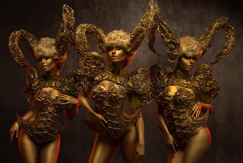 有金黄装饰垫铁的美丽的恶魔妇女 免版税库存照片