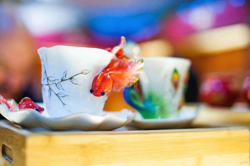 有金黄鱼的白色瓷杯子 图库摄影