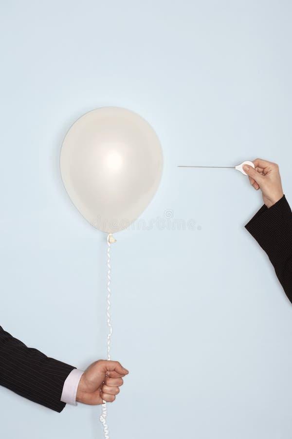 有针和气球的手反对蓝色背景 库存图片