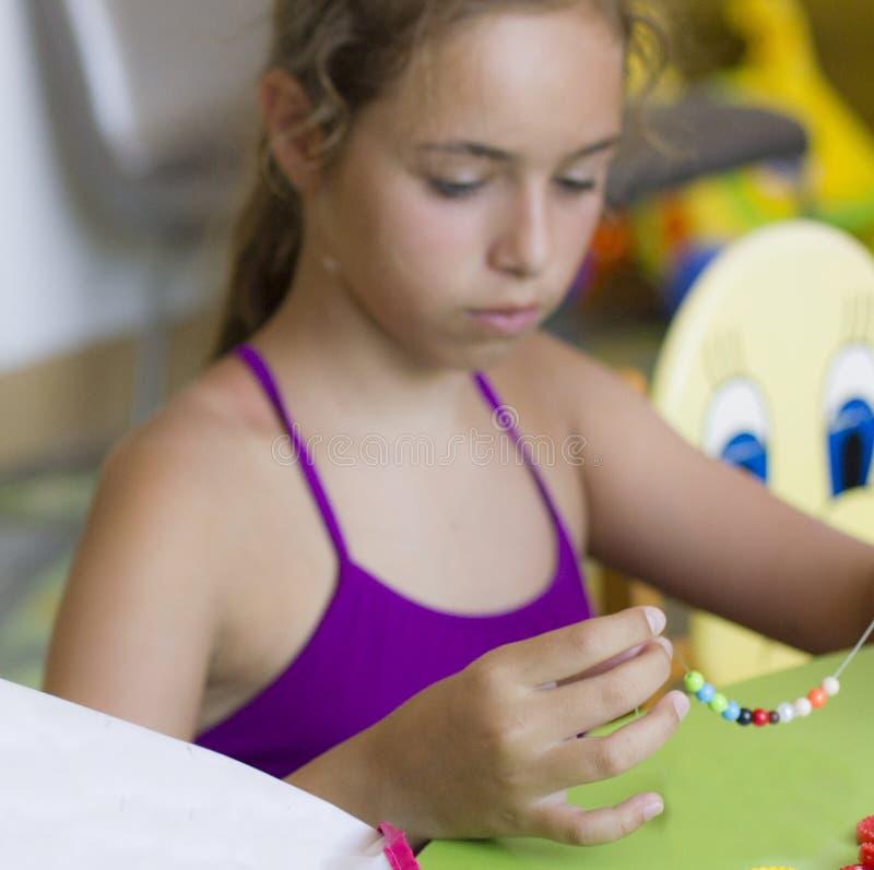 有针线的年轻俏丽的女孩,串起在串成串珠状 图库摄影