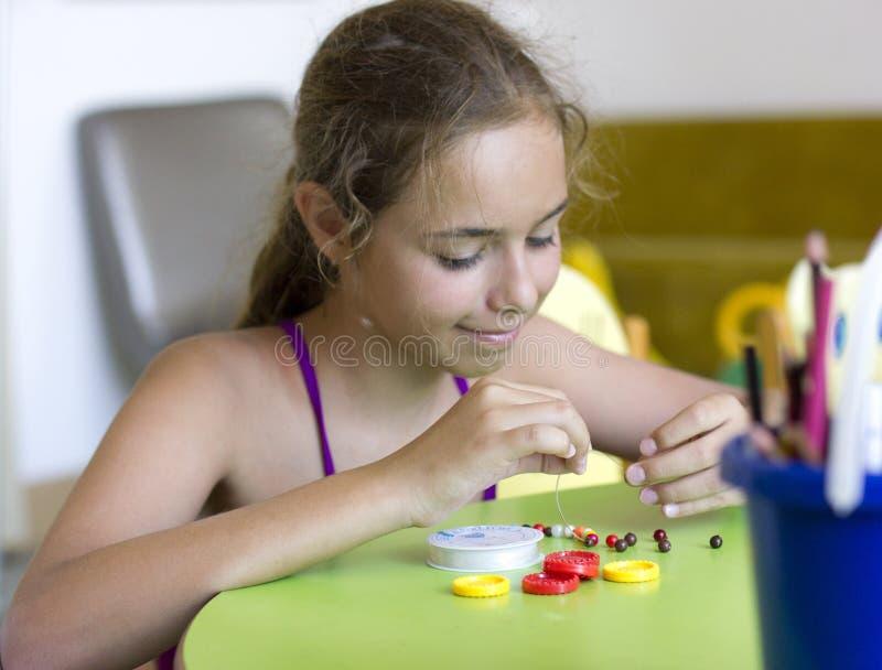 有针线的年轻俏丽的女孩,串起在串成串珠状 库存图片