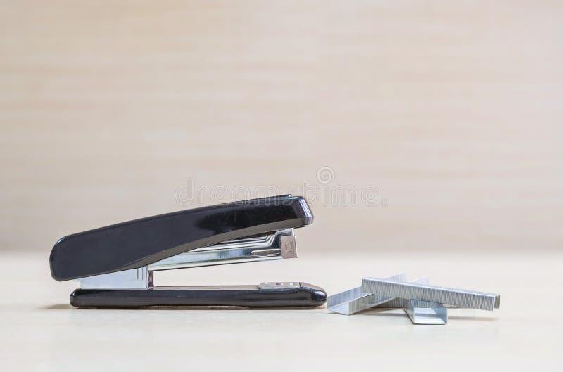 有钉书针的特写镜头黑订书机,在被弄脏的木书桌上的办公设备和墙壁在办公室屋子里构造了背景在风下 免版税库存照片