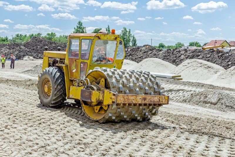 有钉的巨大的压路机在建筑变紧密土壤 库存照片