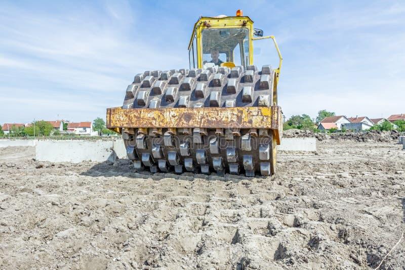 有钉的巨大的压路机在建筑变紧密土壤 图库摄影