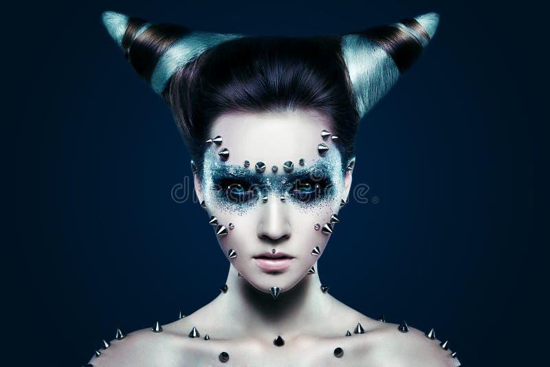 有钉的邪魔女孩在面孔和身体 库存图片