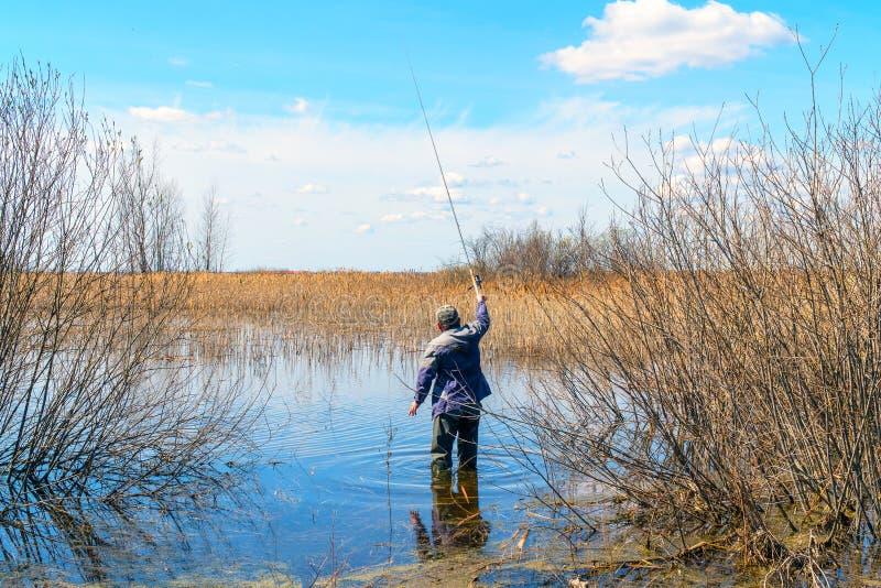 有钓鱼竿的渔夫在水中站立 免版税库存图片