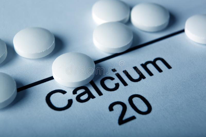 有钙和化学元素钙的题字的白色片剂 库存照片