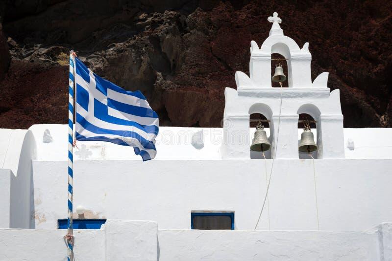 有钟楼的教会和在红色海滩,圣托里尼附近的希腊旗子 库存图片
