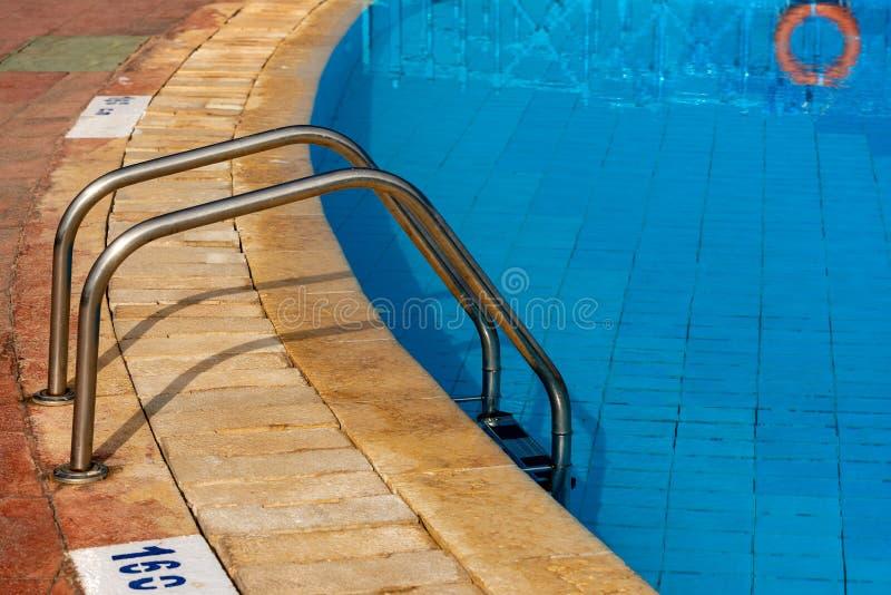 有钢梯子的蓝色游泳场 免版税库存图片