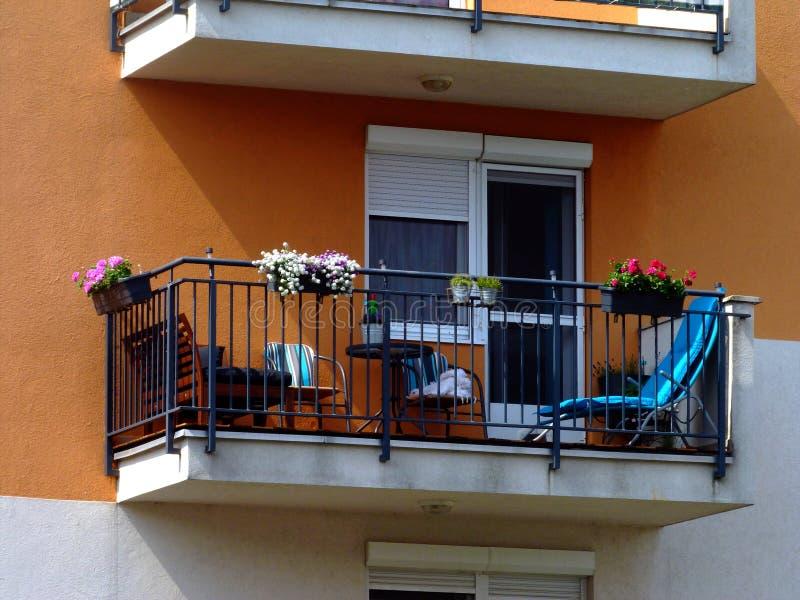 有钢纠察队员栏杆和明亮的露台家具的阳台在夏天 免版税图库摄影