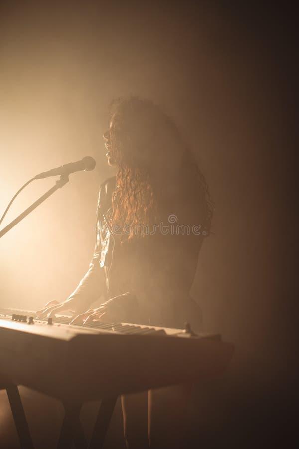有钢琴的女歌手在有启发性夜总会 图库摄影