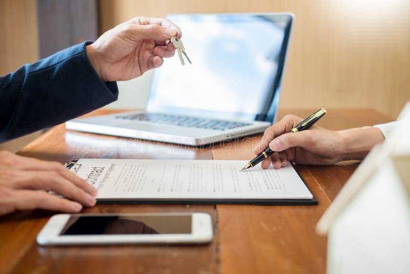 有钥匙的代理顾客不动产房地产经纪商的新房、给公寓钥匙的手或地产商接受人在结束以后 免版税库存照片