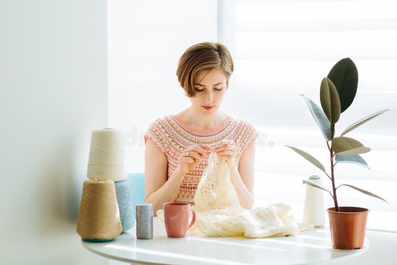 有钩针编织的Сraftswoman编织的礼服在内部舒适的工作场所在家 女性与嫩鞋带一起使用 手工制造的事务 库存照片