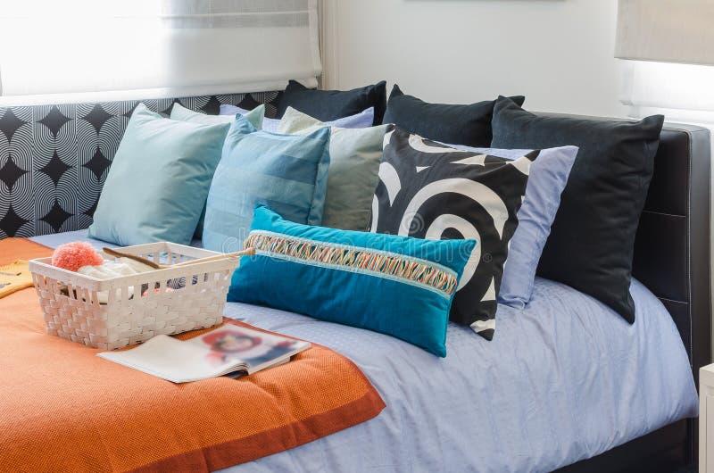 有钩针编织篮子的五颜六色的枕头在床上的 免版税图库摄影