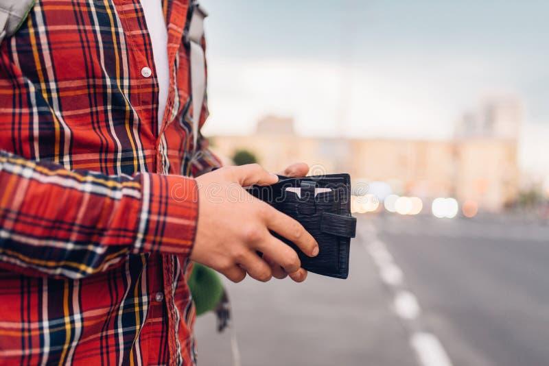 有钱包的男性游人在公共汽车站 库存图片