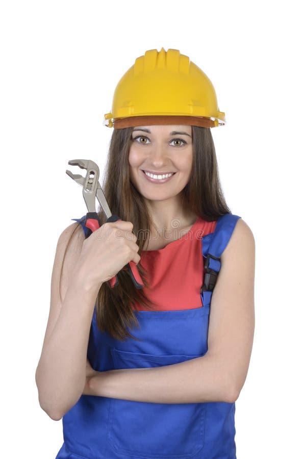 有钳子和安全帽的俏丽的工作者妇女 免版税库存照片
