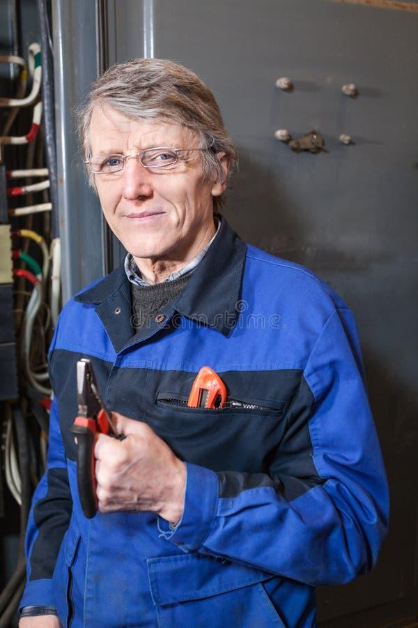 有钳子的成熟电工在他的站立近的高压箱子的手上 免版税图库摄影