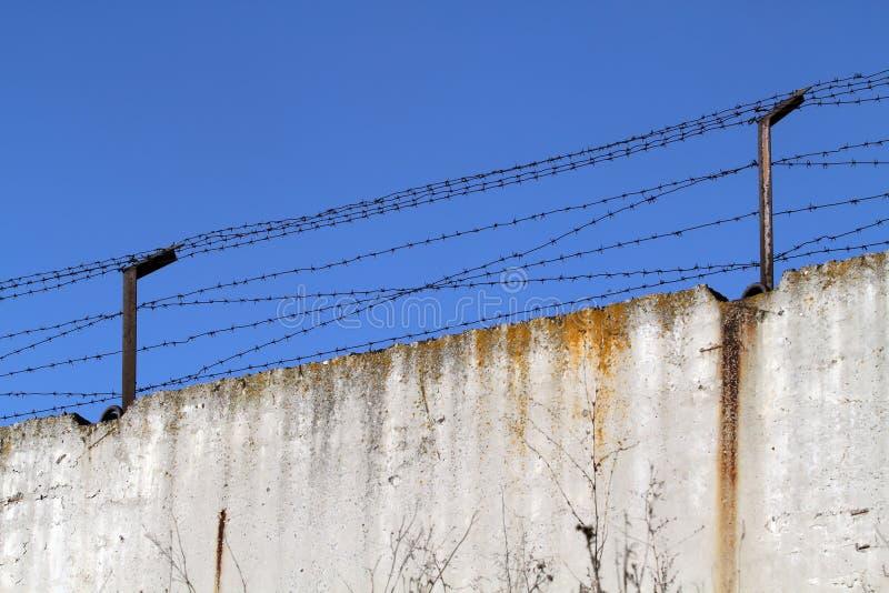 有铁丝网的具体篱芭在明亮的蓝色背景  免版税库存图片