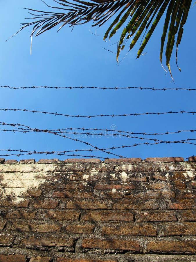 有铁丝网的砖墙,在天空蔚蓝下 库存照片