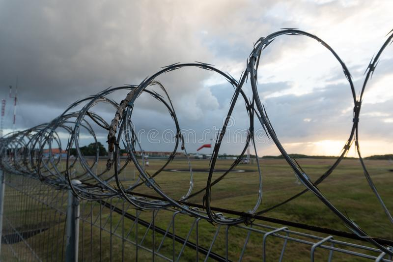 有铁丝网的篱芭在对象的边界在与日出光的多云早晨在夏天,印度尼西亚 免版税库存照片