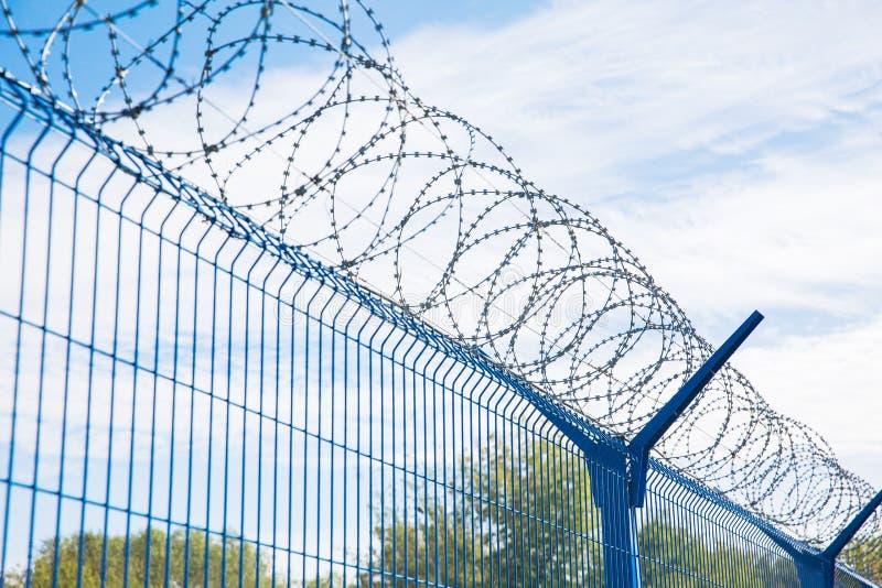 有铁丝网的蓝色篱芭在蓝天背景 危险的区 库存图片