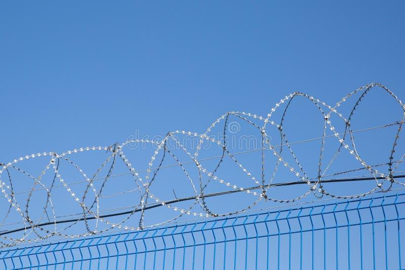 有铁丝网的蓝色篱芭在蓝天背景 危险的区 库存照片