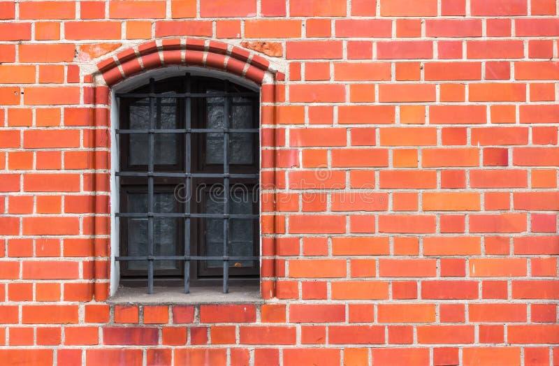 有铁窗口滤栅的红砖墙壁 免版税图库摄影
