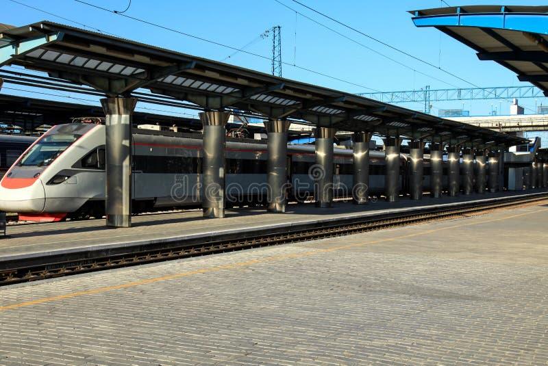 有铁路支架立场的客车在驻地的平台 旅行和旅游业概念、夏天和春天 免版税库存照片
