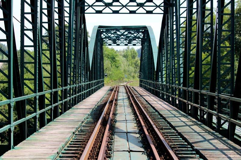 有铁路轨道的绿色金属铁路桥建筑围拢与去往长得太大的森林vegetat的木边路 免版税库存图片