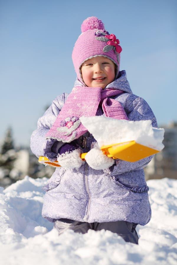 有铁锹的微笑的小女孩在随风飘飞的雪显示雪 免版税图库摄影