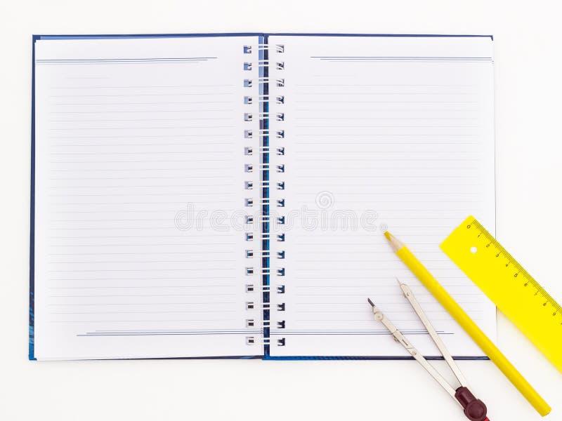 有铅笔、分切器和统治者的螺纹笔记本 库存图片