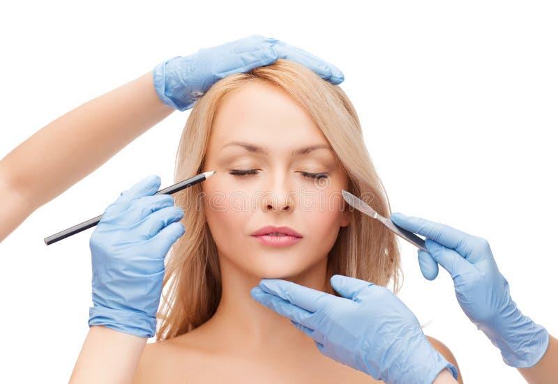 有铅笔和解剖刀的妇女和美容师手 免版税库存照片