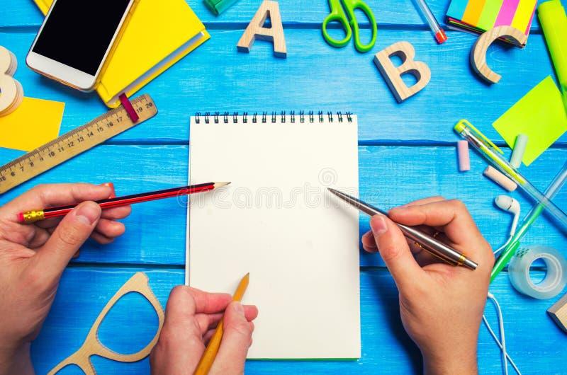 有铅笔的三只手和对一个笔记本的笔尖有在桌面蓝色木背景的白页的 创造性的混乱 免版税库存图片
