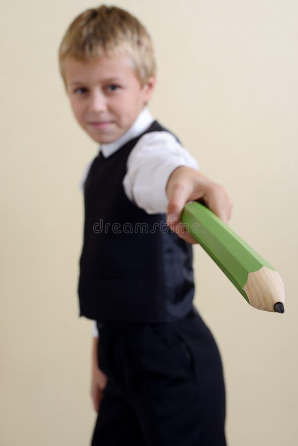 有铅笔的勇敢的男小学生 库存照片