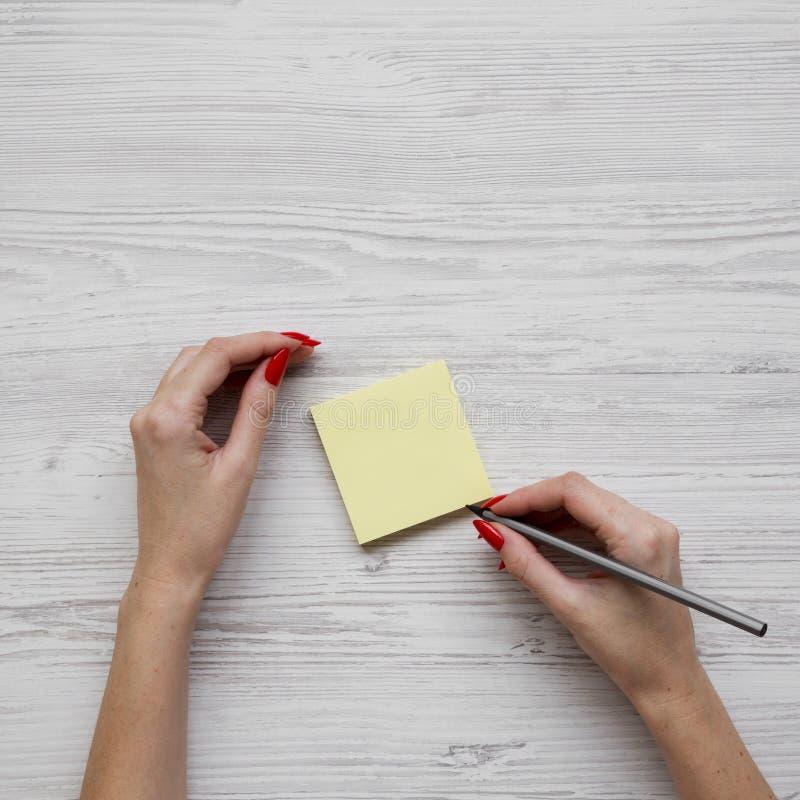 有铅笔的女性工作场所在女性手,贴纸,顶上的看法上 r 免版税图库摄影