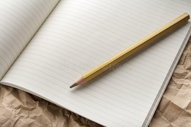 有铅笔的空白的笔记本在木书桌上 免版税库存照片