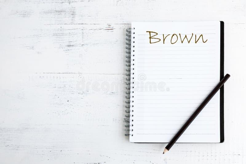 有铅笔的笔记本在木褐色 免版税库存图片