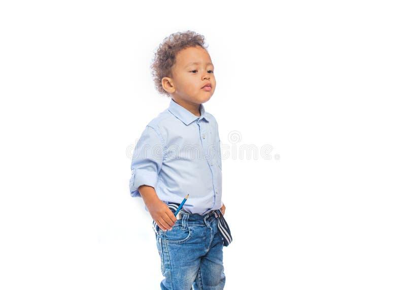 有铅笔的黑人孩子在他的手上看远离他在被隔绝的背景 库存图片