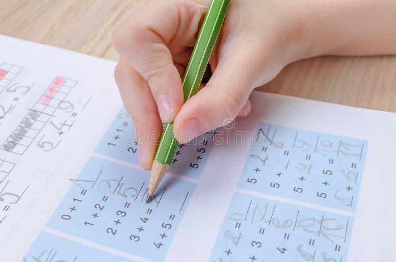 有铅笔,homewortk,算术不正确藏品的儿童的手  免版税库存照片