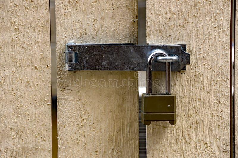 有铰链和挂锁的白色木门 库存图片
