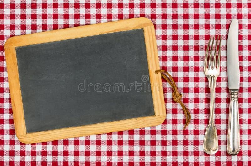 有银器的空的黑板在桌布 免版税库存图片