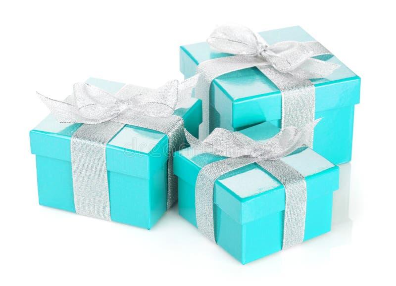 有银色丝带和弓的三个蓝色礼物盒 库存图片