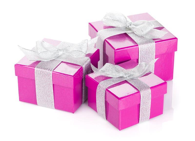 有银色丝带和弓的三个紫色礼物盒 免版税库存图片