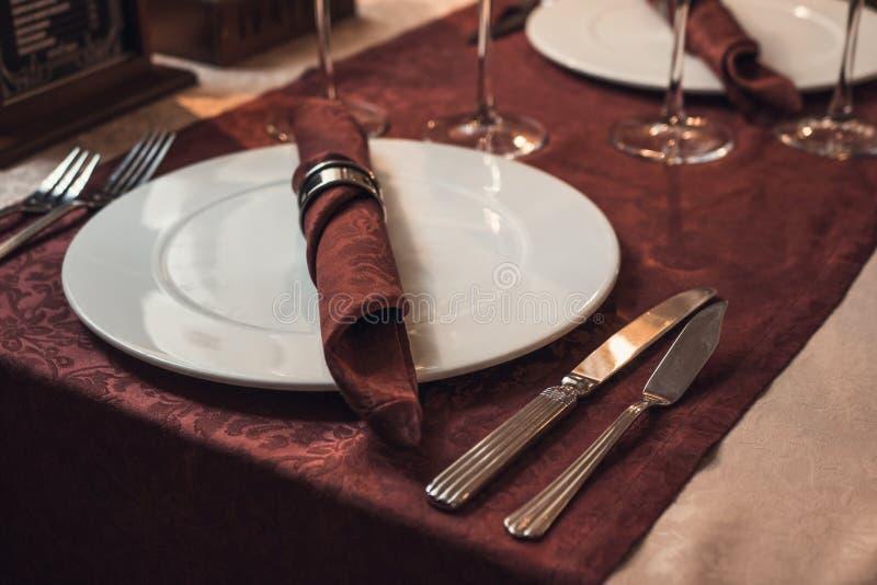 有银色叉子的空的在餐馆桌上的板材和刀子与深紫红色桌布 图库摄影