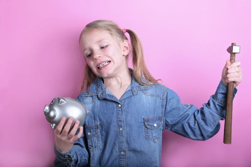 有银色存钱罐和锤子的恼怒的滑稽的少女在桃红色背景 概念货币保存 免版税图库摄影