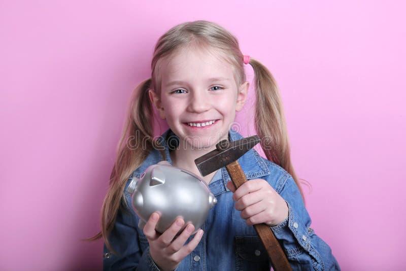 有银色存钱罐和锤子的愉快的少女在桃红色背景 概念货币保存 免版税库存图片