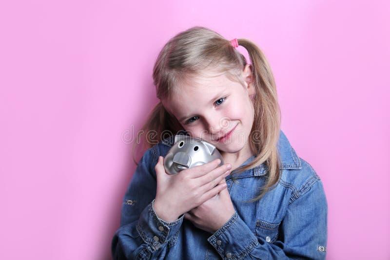 有银色存钱罐的恼怒的滑稽的少女桃红色背景的 概念货币保存 免版税库存照片