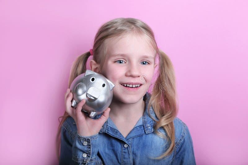 有银色存钱罐的愉快的少女桃红色背景的 概念货币保存 免版税库存图片